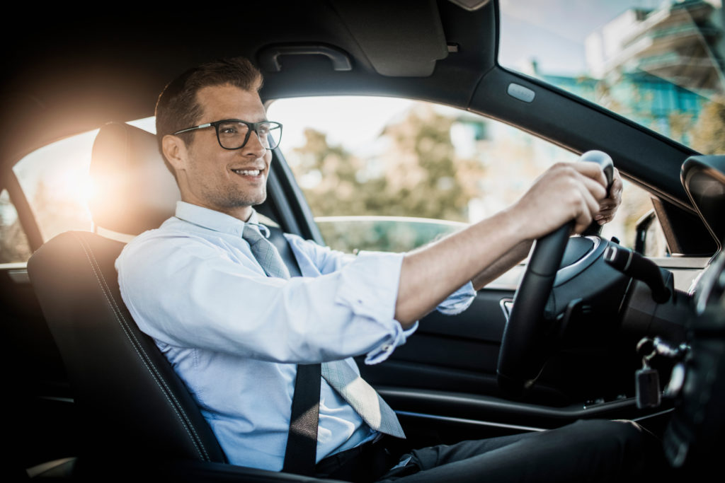 Businessman behind the wheel wearing glasses for driving Essilor Pro-Drive